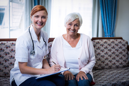 giver: Smiling doctor consulting with senior woman at home Stock Photo