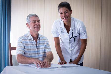 braile: médico femenino que ayuda a los pacientes en la lectura del libro en braille en el hogar