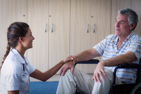 consoling: Female doctor consoling senior man in living room at home Stock Photo