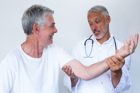 acupressure: Male doctor giving palm acupressure treatment to senior man in hospital Stock Photo