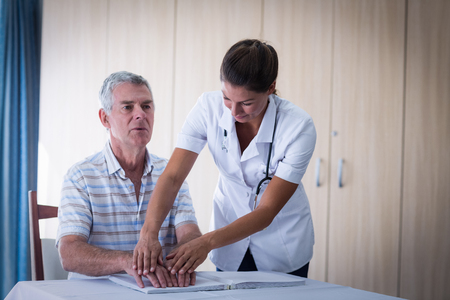 braille: médico femenino que ayuda a los pacientes en la lectura del libro en braille en el hogar