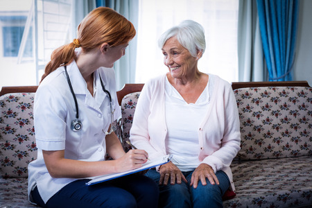 giver: Doctor consulting with senior woman at home