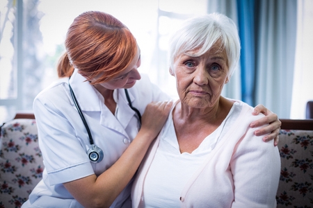 consoling: Doctor consoling senior woman at home