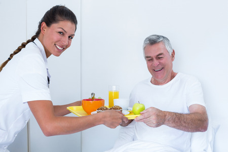 doctor giving glass: Female doctor serving breakfast to senior man in hospital Stock Photo