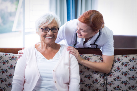 consoling: Smiling doctor consoling senior woman at home Stock Photo