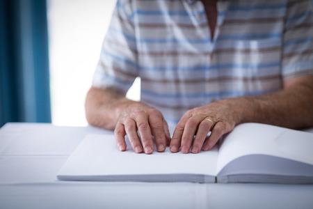braile: ciego que lee un libro en braille en el hogar Foto de archivo