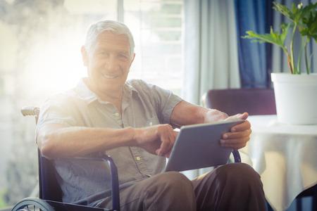 visualizing: Happy senior man on wheelchair using digital tablet at home Stock Photo