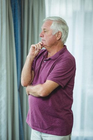 grey hair: Portrait of thoughtful senior man standing with hand on chin