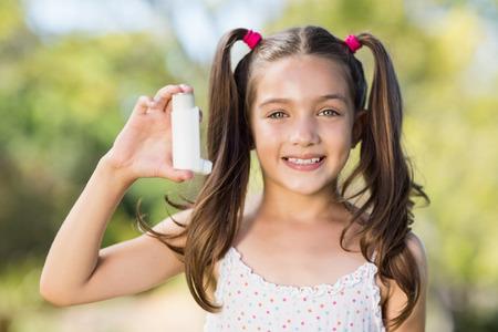 inhaler: Portrait of girl holding an asthma inhaler in the park Stock Photo
