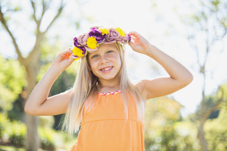 girl holding flower: Portrait of cute young girl holding flower wreath and smiling in park