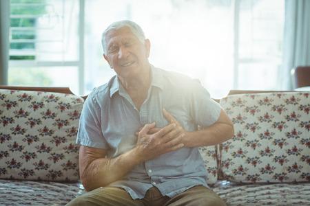 dolor de pecho: Hombre mayor que sufre de un dolor en el pecho en casa Foto de archivo