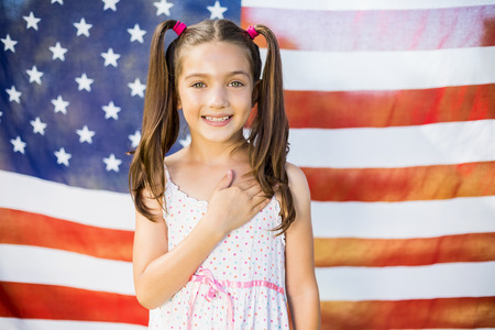 Portrait of young girl standing in front of American flag