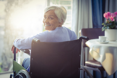 happy woman: Portrait of smiling senior woman senior woman sitting on wheelchair at home Stock Photo