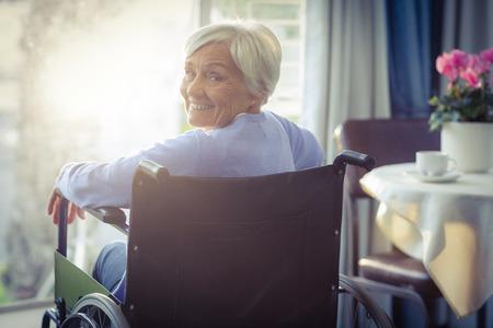 persona en silla de ruedas: Retrato de la mujer mayor sonriente mujer mayor que se sienta en la silla de ruedas en el hogar