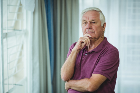 abode: Portrait of thoughtful senior man standing with hand on chin