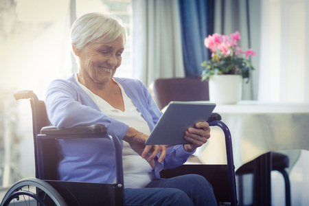 wheelchair woman: Happy senior woman on wheelchair using digital tablet at home Stock Photo