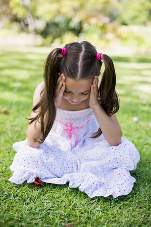 hand on forehead: Upset girl sitting with hand on forehead in park Stock Photo