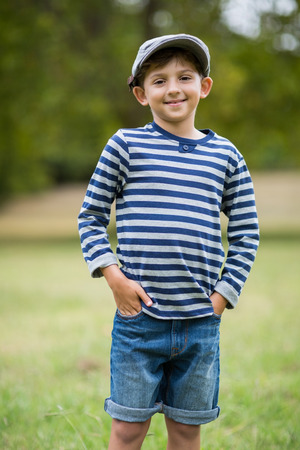 hands on pocket: Portrait of smiling boy standing with hands in pocket in park