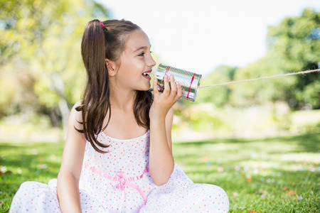 tin can phone: Cute young girl speaking through tin can phone in park