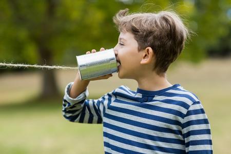 tin can phone: Cute boy speaking through tin can phone in park Stock Photo
