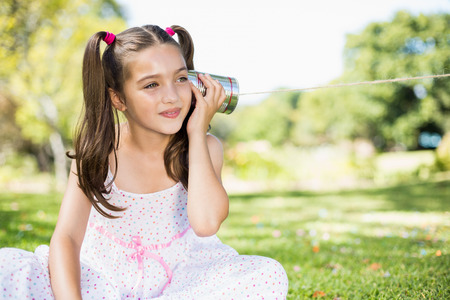 tin can phone: Cute young girl listening through tin can phone in park Stock Photo