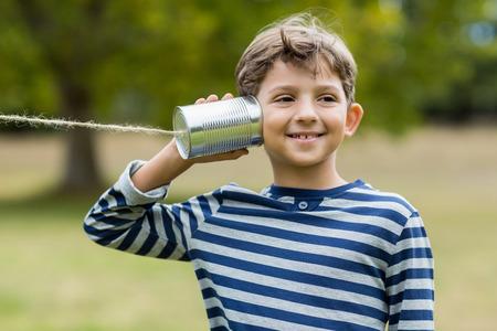 tin can phone: Cute boy listening through tin can phone in park
