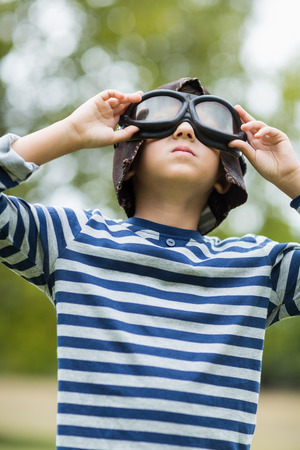 child looking up: Boy pretending to be an aviation pilot in park Stock Photo