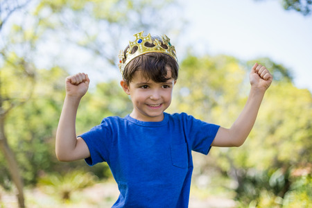 clenching fists: Boy wearing a crown and clenching his fists in excitement in park Stock Photo