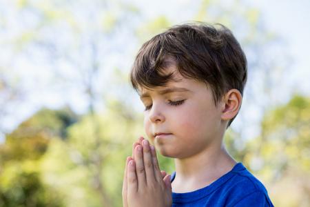 公園における閉眼祈りの少年のクローズ アップ