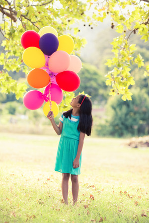 weekend activity: Girl holding a balloon in park on a sunny day