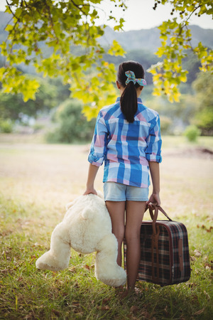 rear view girl: Rear view of a girl standing in the park with a teddy bear and suitcases