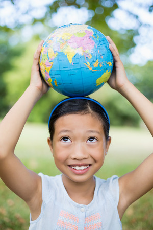 global retirement: Smiling girl carrying a globe on her head in the park