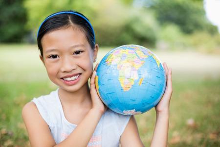 shoulder carrying: Portrait of smiling girl carrying a globe on her shoulder in the park