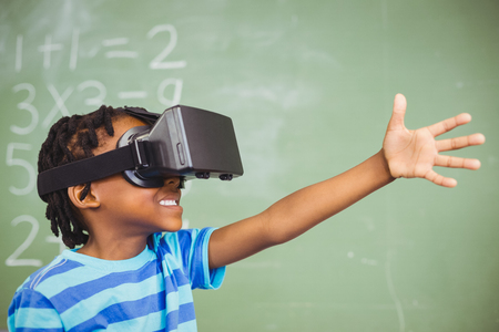 School boy in virtual reality glasses in classroom at school