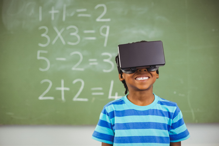 virtual school: School boy in virtual reality glasses in classroom at school