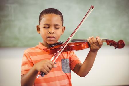 schoolboy: Schoolboy playing violin in classroom at school Stock Photo