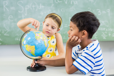 School kids looking at globe in classroom at school