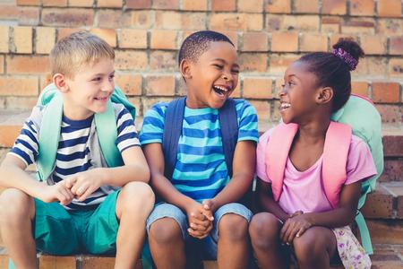 Boldog iskolás gyerek ül össze a lépcsőházban az iskolában