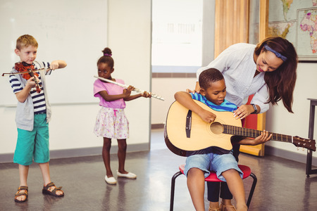 school work: Teacher assisting a kids to play a musical instrument in classroom at school Stock Photo