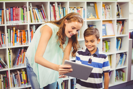 Teacher and school boy using digital tablet in library at school Stock Photo