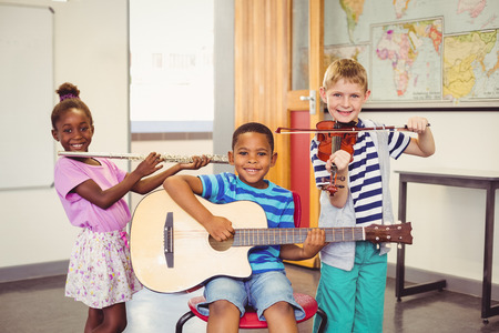 boy playing guitar: Portrait of smiling kids playing guitar, violin, flute in classroom at school