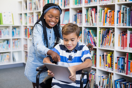 Happy schoolgirl standing with schoolboy on wheelchair using digital tablet in library