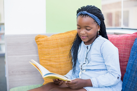 joy of reading: Schoolgirl sitting on sofa and reading book in library Stock Photo