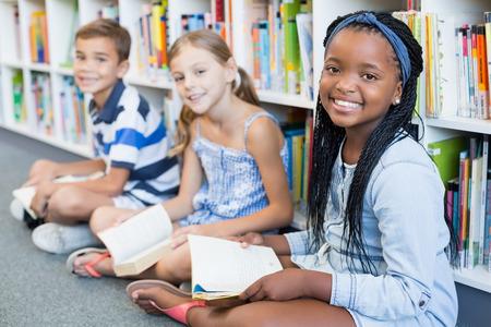Portret van glimlachende schooljonge geitjes die op vloer zitten en boek in bibliotheek lezen Stockfoto