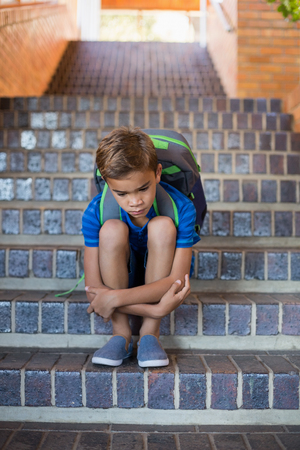 desolación: Sad schoolboy sitting alone on staircase at school