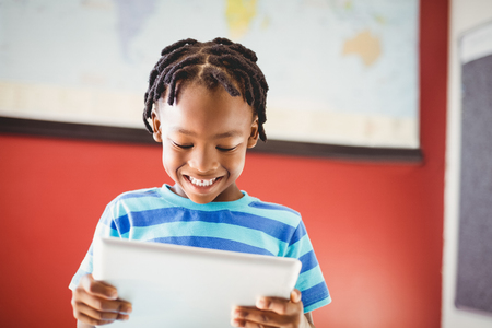 joy of reading: Happy schoolboy using digital tablet in classroom at school