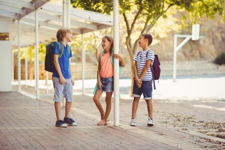 Lachende schoolkinderen die in de gang staan en elkaar op school praten