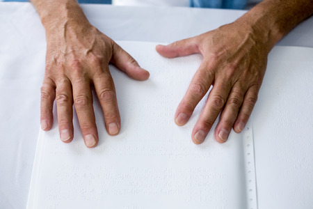 braille: Senior using braille to read in a retirement home