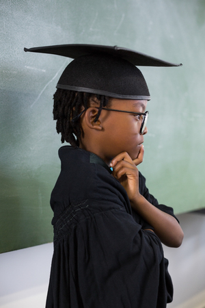academic dress: Thoughtful schoolboy wearing graduation gown in classroom at school Stock Photo