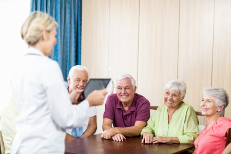 sheltered accommodation: Seniors listening to nurse with tablet in a retirement home